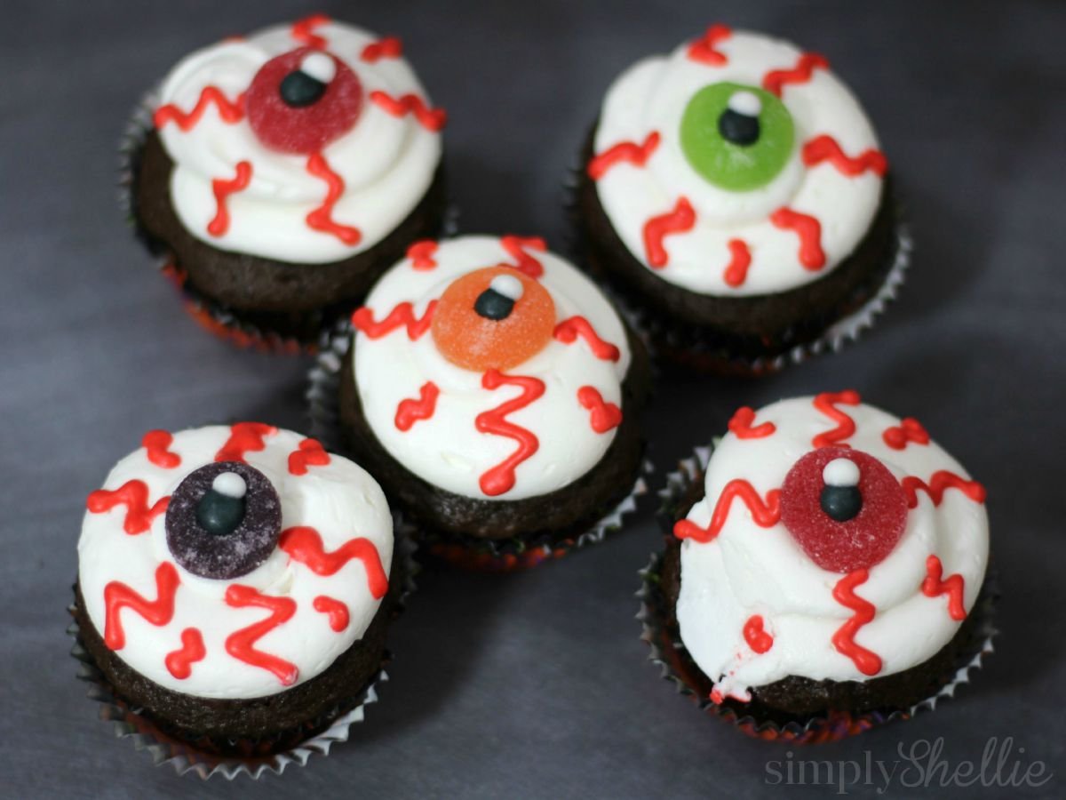 For black cat cupcakes, use chocolate or black-tinted frosting plus red licorice whips for whiskers and bright green Skittles for eyes. Alphabet-shaped cereal lets verbally-oriented kids turn each cupcake into a dialogue bubble or blackboard.